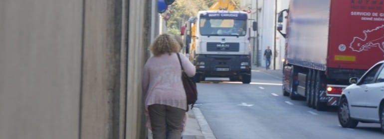 Una mujer camina por una acera angosta en Barcelona.