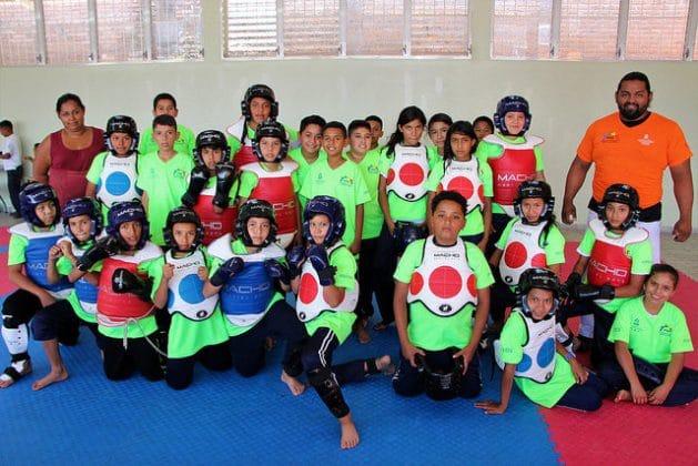 Parte del grupo de niños que practican taekwondo, junto a un instructor y una de las madres. Su alegría prueba que los cambios en los empinados barrios marginales de Tegucigalpa son posibles, si se invierte en dignificarlos. Crédito: Thelma Mejía/IPS